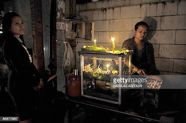 A woman buys a grilled sausage at a street during a blackout in a popular area of Bangkok on April 9 2009 About 100 taxi drivers loyal to fugitive...