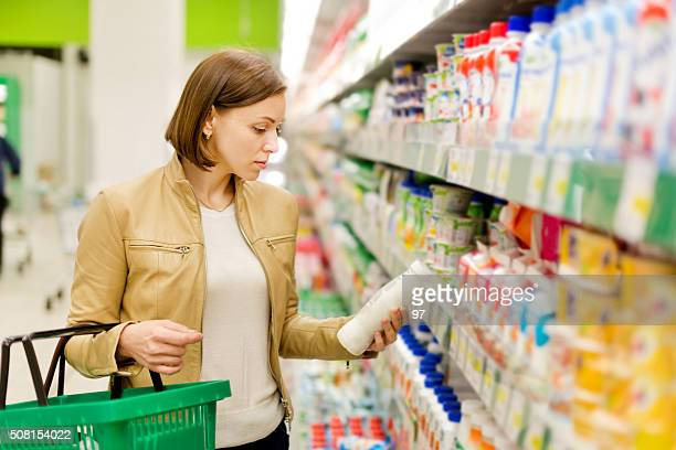 woman buys a milk - labeling stock photos and pictures