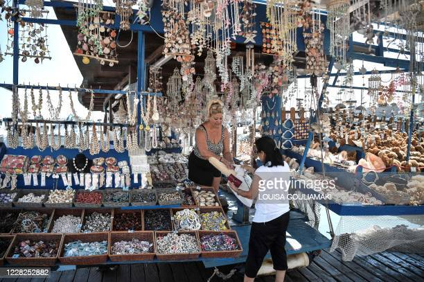 A woman buys a natural sponge at a seashells shop on the Aegean island of Rhodes on August 29 2020 Rhodes island one of the mass tourism Greek...