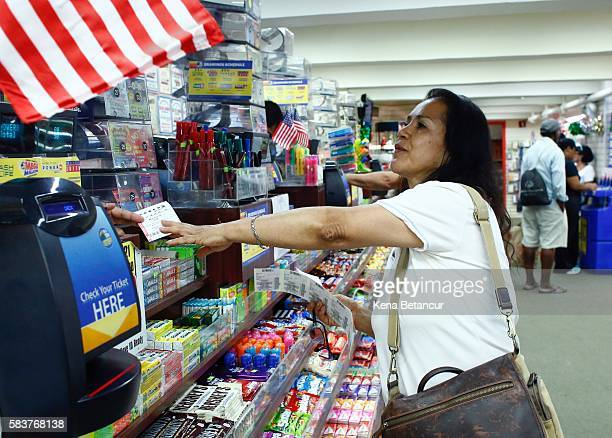A woman buys a powerball lottery ticket at a store in Penn Station on July 27 2016 in New York City The Powerball drawing on Wednesday will give...
