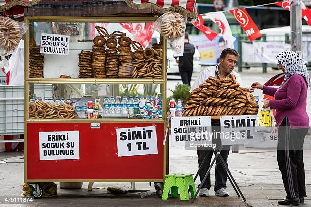 A woman buys a simit bread snack from a street vendor in the Besiktas district of Istanbul Turkey on Friday May 29 2015 President Recep Tayyip...