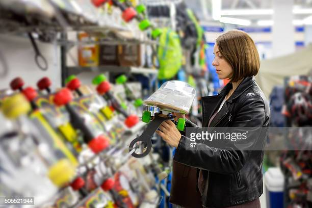 woman buys a skateboard in a sports shop - sports equipment stock pictures, royalty-free photos & images