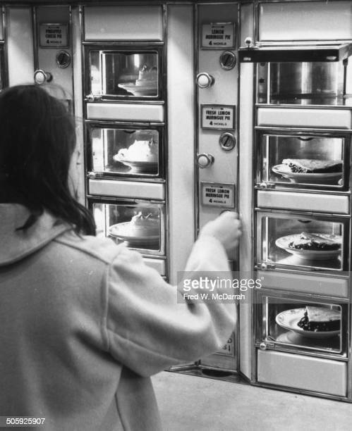 A woman buys a slice of lemon meringue pie at a Horn and Hardart automat cafeteria New York New York January 18 1964