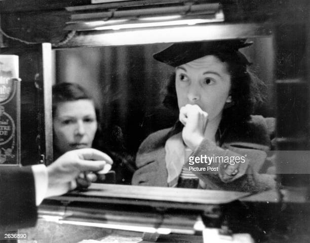 Woman buys a ticket at a theatre box office. Original Publication: Picture Post - 126 - Box Office - pub. 1939