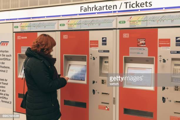 Frau kauft ein Ticket für den öffentlichen Verkehr in einem Automaten