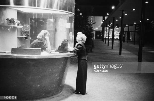 A woman buys a ticket to a film at the Egyptian Theatre on Hollywood Boulevard Los Angeles 1951 Original Publication Picture Post 5298 Two Men In...