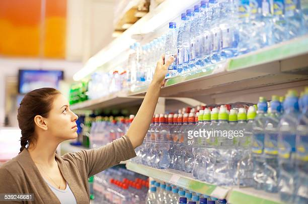 woman buys a water bottle in shop