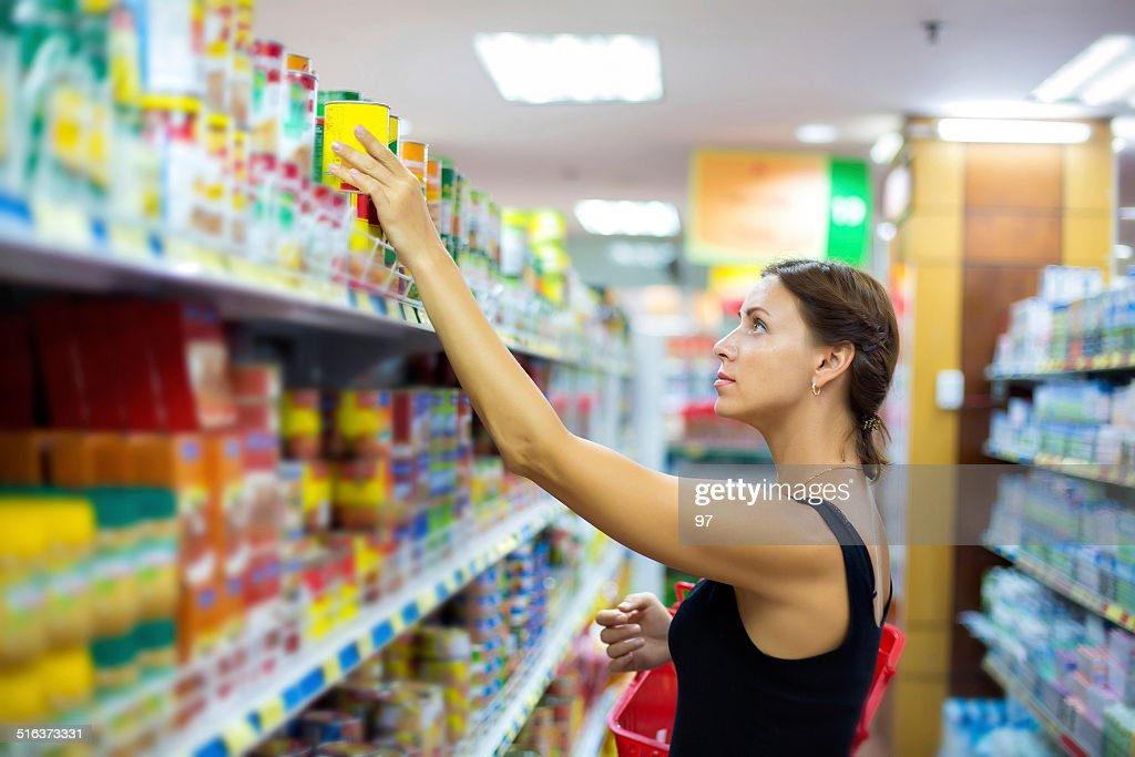 woman buys canned : Stock Photo