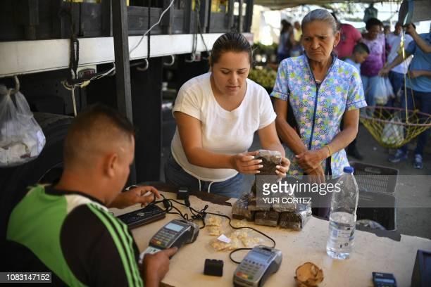 Woman buys coffee at the vegetables market in Caracas, Venezuela on January 15, 2019. - The president of Venezuela, Nicolás Maduro, increased the...
