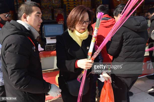 A woman buys fireworks at a stall on the outskirts of Beijing in the buildup to Lunar New Year celebrations on February 13 2018 Beijing has banned...