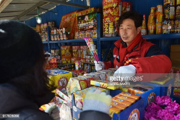 A woman buys firworks at a stall on the outskirts of Beijing in the buildup to Lunar New Year celebrations on February 13 2018 Beijing has banned...