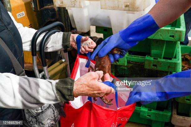 A woman buys fresh crab from a fishing boat as it returns to the harbour in Scarborough UK on Tuesday June 2 2020 The threat of a nodeal Brexit is...