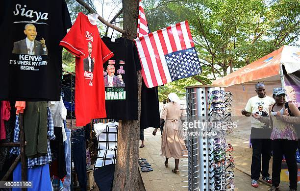 MCCONNELL*** A woman buys glasses next to a shop selling tshirts with a depiction of US President Barack Obama at the Kogelo market on July 13 2015...