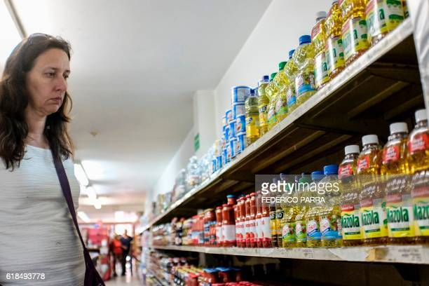 A woman buys goods at a supermarket in Caracas on October 20 2016 Hit by the fall of global oil prices the economy in Venezuela has crashed and food...