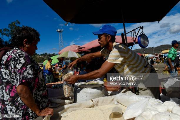 A woman buys groceries at the municipal market of Coche a neighbourhood of Caracas on June 20 2018 Venezuelan President Nicolas Maduro ordered the...