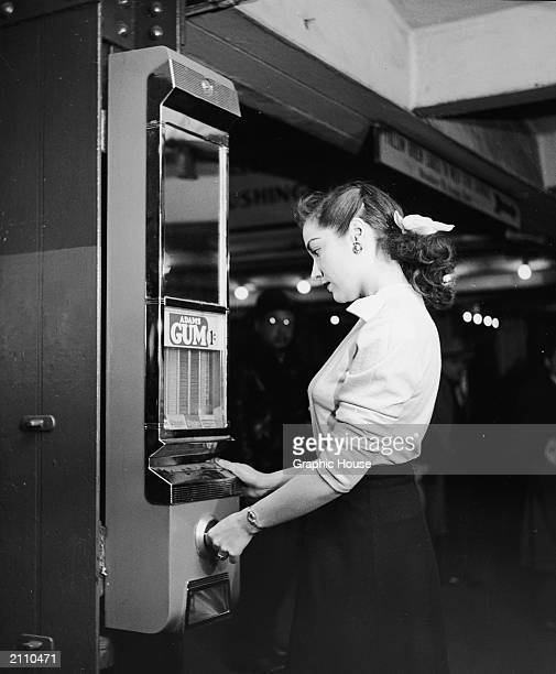 A woman buys gum from a wall mounted vending machine 1950s