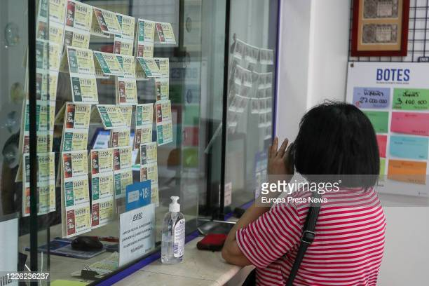 Woman buys lottery in an Administration in Manises during the fourth day since the reopening of her business within the de-escalation process...