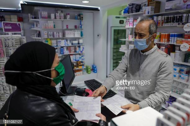 Woman buys medicine at a pharmacy in the Lebanese capital Beirut, on February 2, 2021. - With the economy in a tailspin and the COVID-19 pandemic...