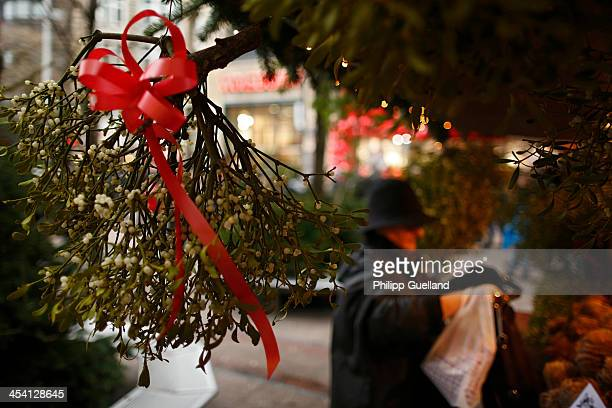 A woman buys mistletoes at a stall on the christmas market in the main pedestrian street on December 7 2013 in Hamburg Germany According to a recent...