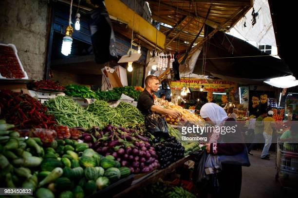 A woman buys onions from a trader's stall at a local market in downtown Amman Jordan on Thursday June 21 2018 President Trump and First Lady Melania...