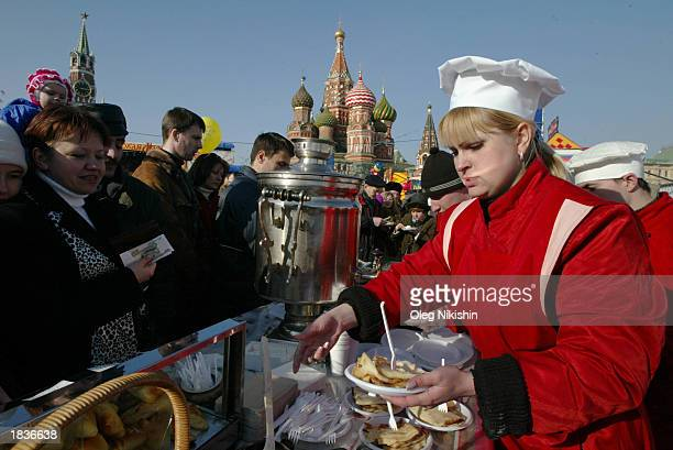 Woman buys pancakes at Red Square during Maslenitsa, or Shrovetide, festivities with St. Basil Cathedral and the Spassky Tower in the background,...