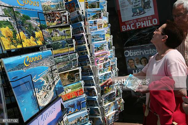 A woman buys postcards on the Croisette a day before the start of the 62nd edition of the Cannes Film Festival on May 12 2009 Cannes will add a new...