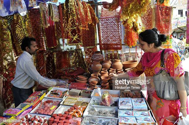 A woman buys ritual things from a roadside shop a day before the Navratri festival starts at Sector 27 market on March 30 2014 in Noida India...