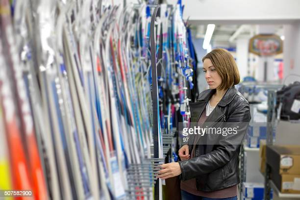 woman buys skis - sports equipment stock pictures, royalty-free photos & images