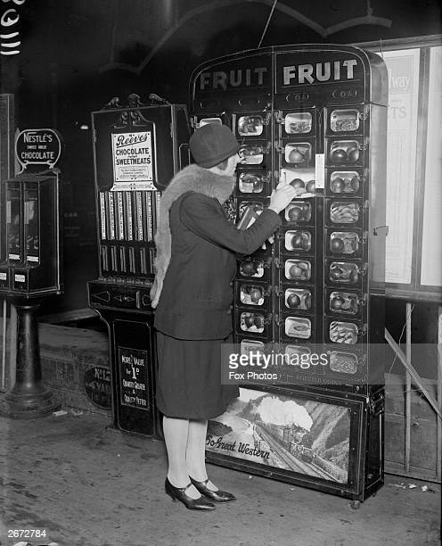 Woman buys some fruit from a coin-operated vending machine at Paddington Station, London.