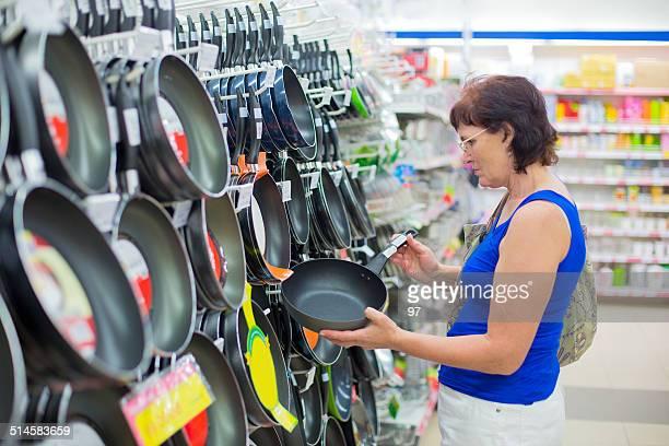 frau kauft der pfanne - küchenbedarf stock-fotos und bilder