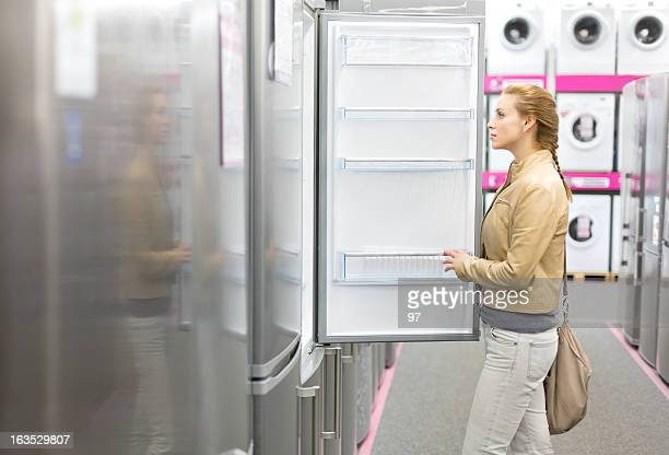 woman buys the refrigerator in shop.