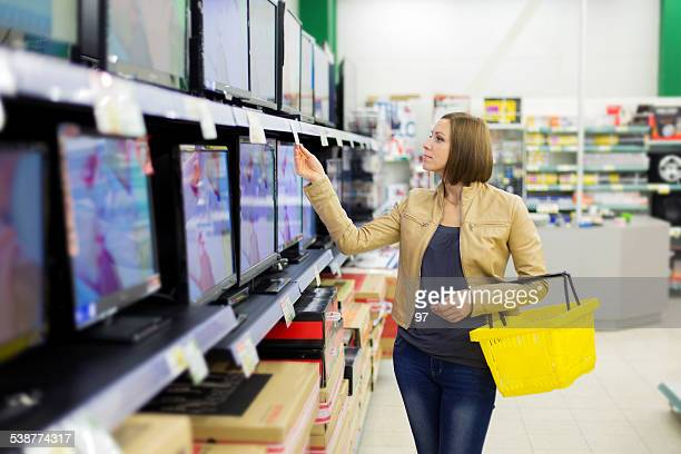 woman buys the tv - electronics store stock photos and pictures