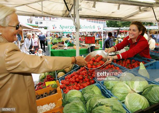 A woman buys tomatos at a vegetable market on July 27 2005 in Luneburg Germany Sparked by the election manifesto of the opposition party CDU Germany...