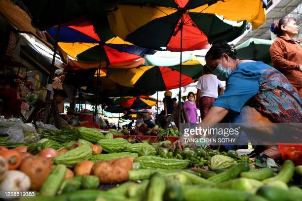 Woman buys vegetables at a market in Phnom Penh on September 15, 2020. - Coronavirus-ravaged economies across the Asia Pacific region are expected to...
