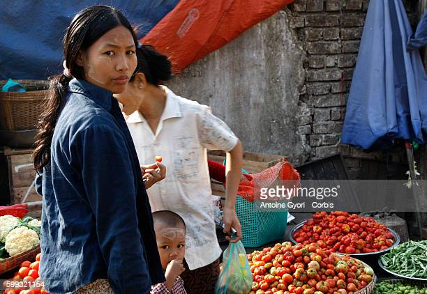 A woman buys vegetales at a market in Yangon She is wearing Thanaka on her face All over Myanmar Burmese are using Thanakaa a bark paste that the...