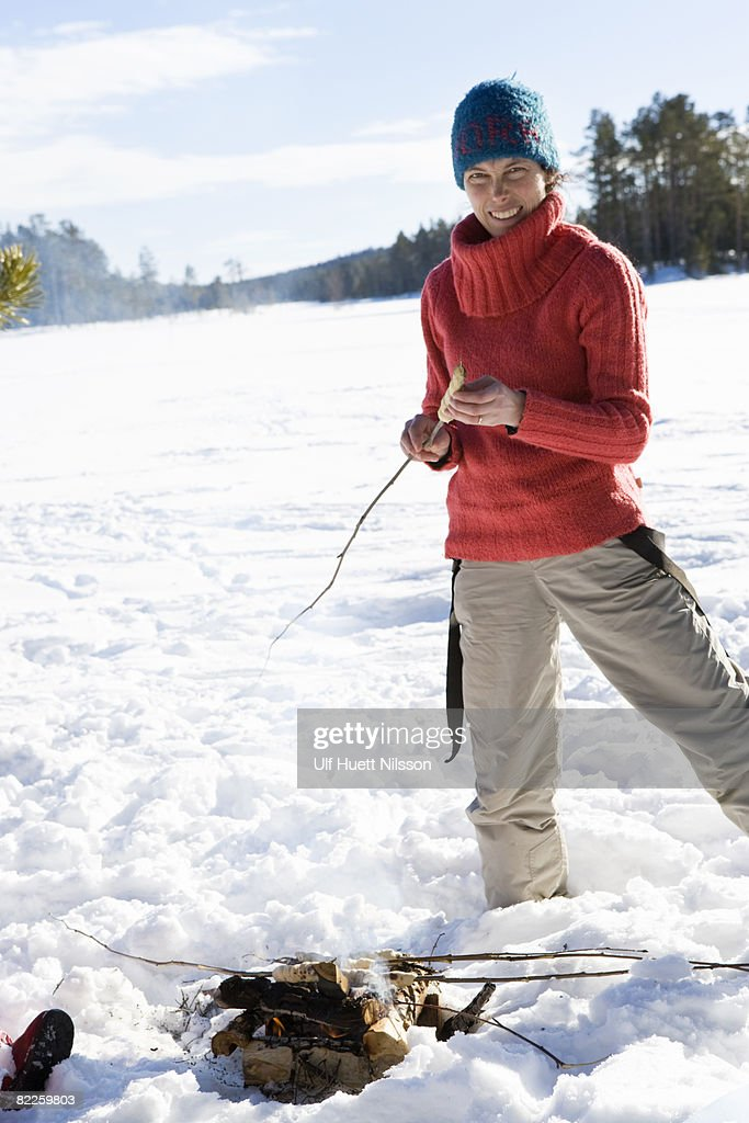 A woman by a bonfire in the snow Sweden. : Stock Photo