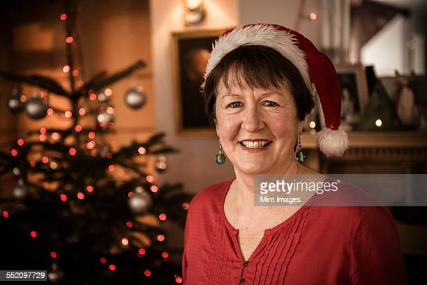 a woman by a christmas tree wearing a santa hat. - hat stock pictures, royalty-free photos & images
