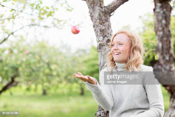 woman by a tree playing with an apple