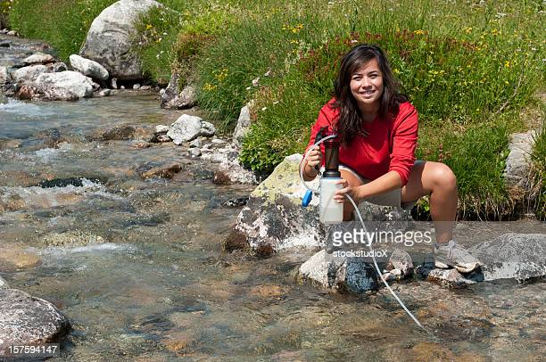 A woman by a water source demonstrating water filtration