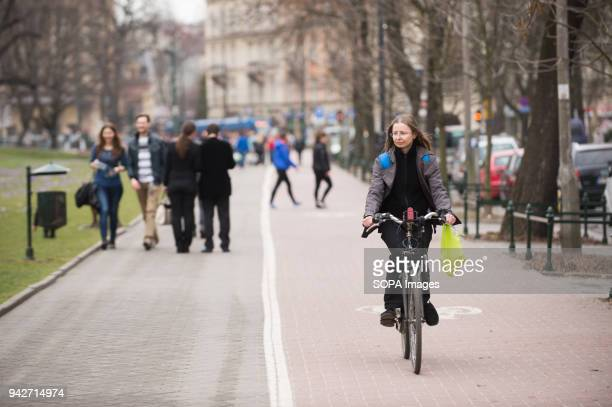 A woman by bicycle is seen next to Wawel Castle in Krakow Poland is a country located in central eastern europe neighbouring Germany to the west and...