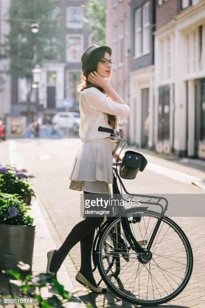 Vrouw met de fiets in Amsterdam stad