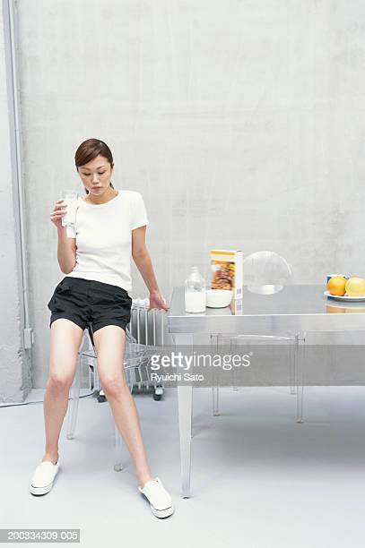Woman by breakfast table holding glass of milk, looking down