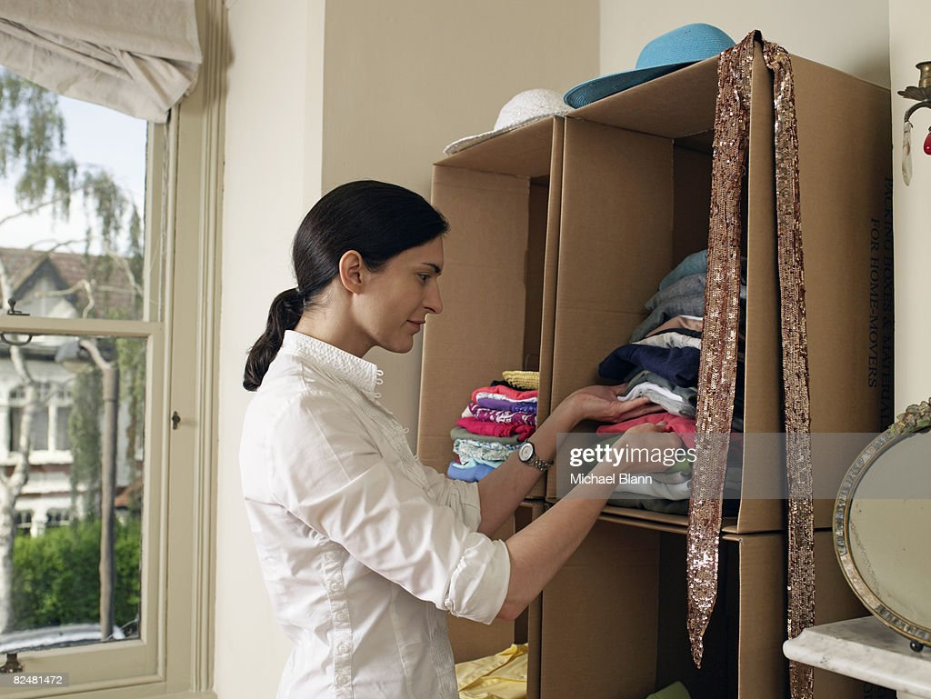 Woman by cardboard box wardrobe : Stock Photo
