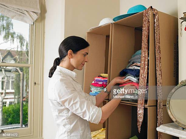 woman by cardboard box wardrobe - tidy room stock pictures, royalty-free photos & images