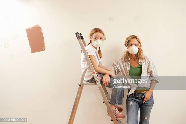 Woman by daughter (8-10) on ladder, wearing dust masks, portrait