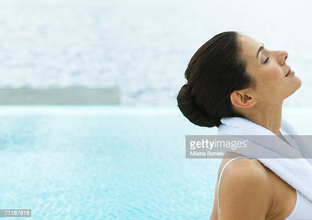 Woman by edge of water with head back and eyes closed