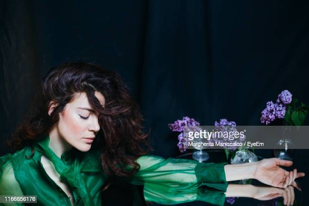 woman by flowers in vase on table against black background - glicine foto e immagini stock