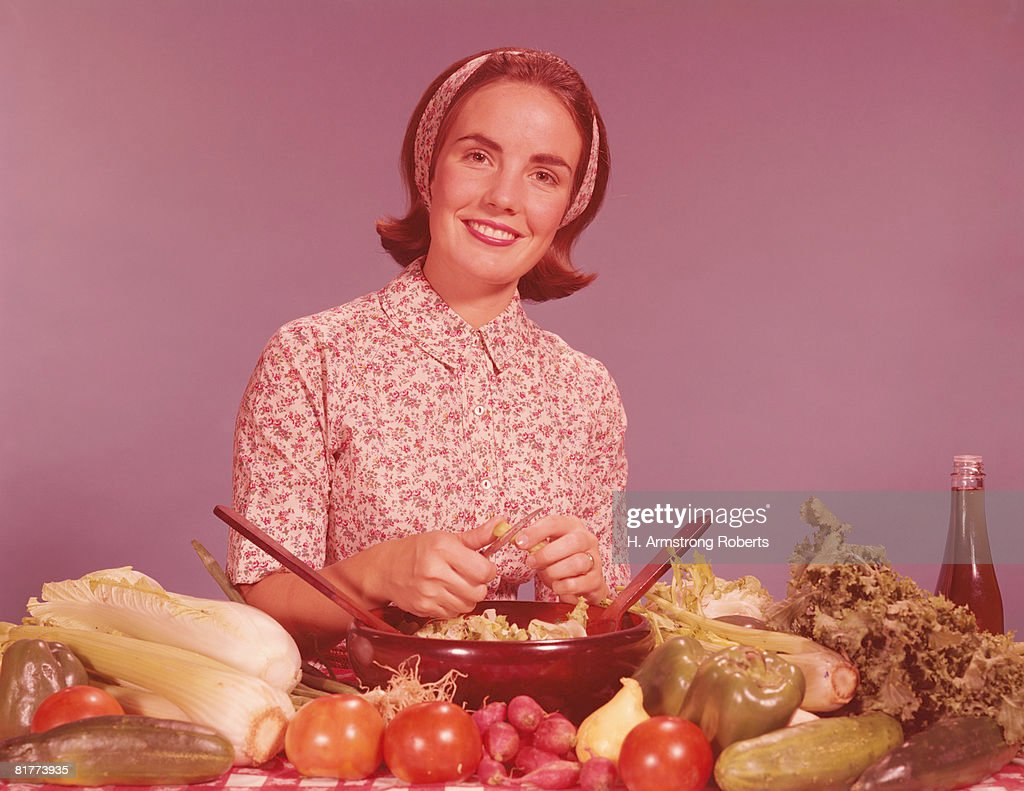 Woman by kitchen counter, tossing vegetables for salad. (Photo by H. Armstrong Roberts/Retrofile/Getty Images) : Bildbanksbilder