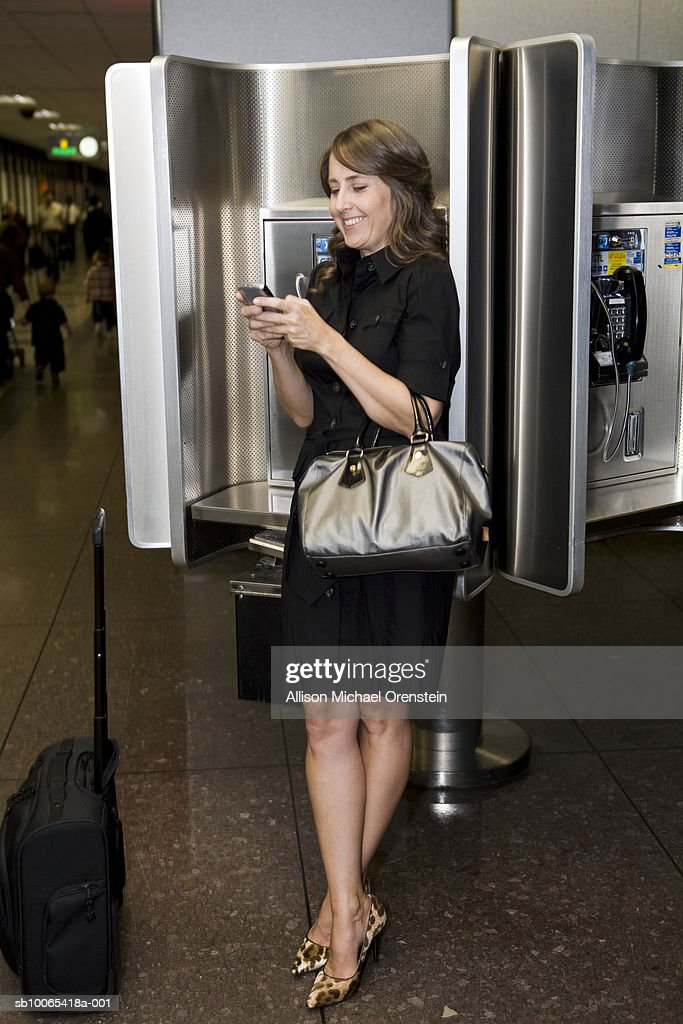 Woman by phone booth at airport texting on cell phone : Foto stock