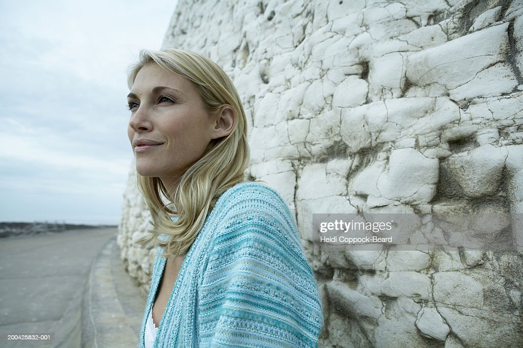 Woman by rock wall, sea in background : Stock Photo